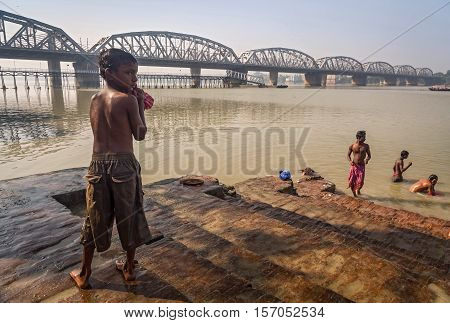 KOLKATA, INDIA - NOVEMBER 13, 2016: Street kid after a bath in the river ganges at Dakshineshwar bathing ghat with the Bally bridge ( Vivekananda Setu) at the backdrop.