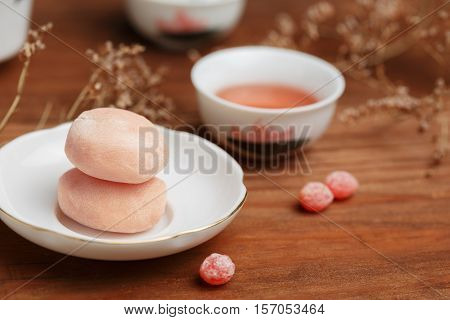Tasty fruit mochi cakes in white porcelain saucer with chinese cup of tea at the background candy drops and dried flowers around stand at brown wooden table. Shallow dof. Focus on cakes.