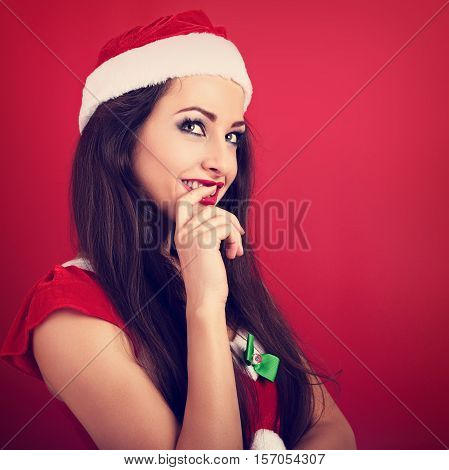 Flirting Coquette Woman In Santa Claus Christmas Costume Looking Up With Finger At Lips On Red Backg