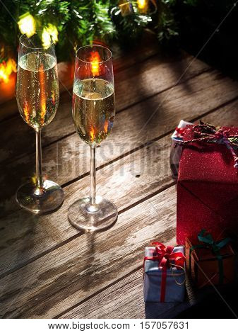 view of two glasses  of champagne with gift boxes on color back