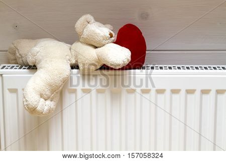 teddy bear with a heart on an iron heated drying radiator battery