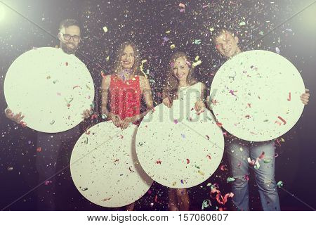 Two beautiful young couples enjoying new year's eve party and holding blank cardboard