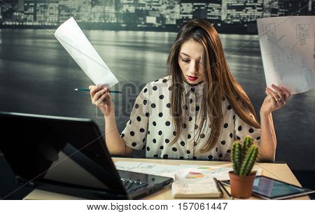 A studio shot of a beautiful woman works in economical sphere. She's got a hard work impasse and have a stress. She's throwing out documents. Black laptop, tablet, documents and little cactus on her office table before city wallpaper