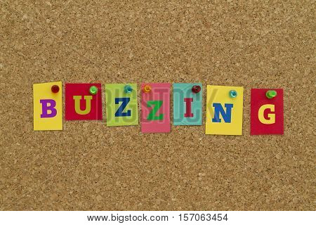 Buzzing word written on colorful sticky notes pinned on cork board.