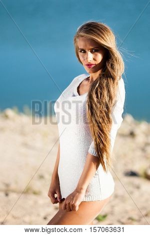 Happy long hair woman on beach in a short white dress.