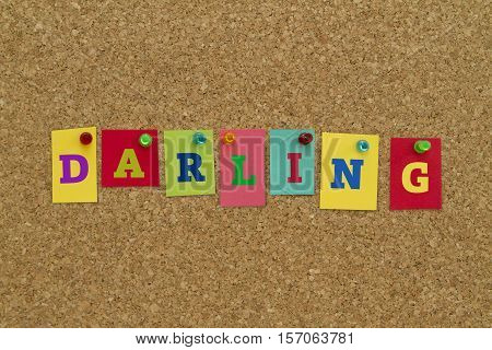 Darling word written on colorful sticky notes pinned on cork board.