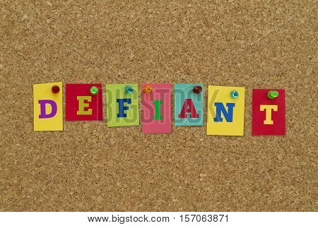 Defiant word written on colorful sticky notes pinned on cork board.