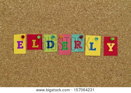 Elderly word written on colorful sticky notes pinned on cork board.