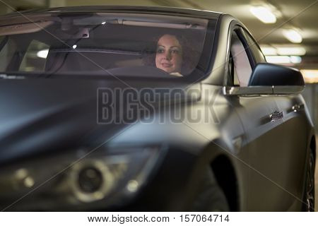 Smiling woman sits in modern car at underground parking.