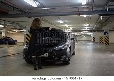MOSCOW, RUSSIA - NOV 11, 2015: Young woman (with model release) shuts down hood of the Tesla S car. The Tesla Model S produced by Tesla Motors, and introduced in June 2012.