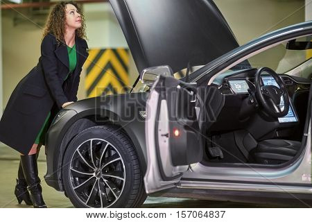 MOSCOW, RUSSIA - NOV 11, 2015: Young woman (with model release) examines inner surface of hood of the Tesla S car. The Tesla Model S produced by Tesla Motors, and introduced in June 2012.