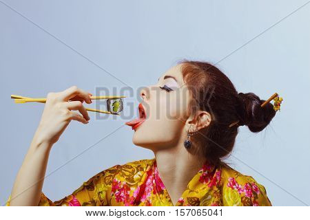Young beautiful woman eating sushi over white background