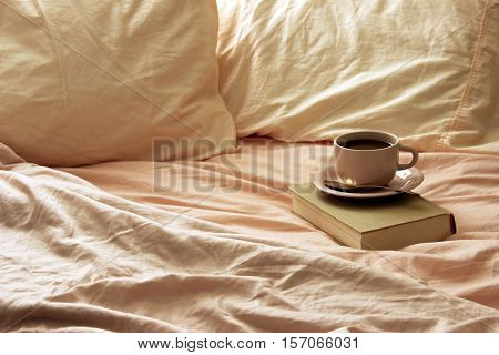 Rumpled bedsheets open to coffee cup and saucer on vintage book. Room for copy.