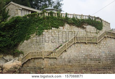 A stone staircase and rock wall on 1000 step beach on the island of Putuoshan in Zhejiang province China.