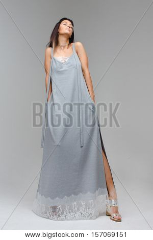 Model which enjoys and lifted her head up, thrusting one leg in a Light long dress