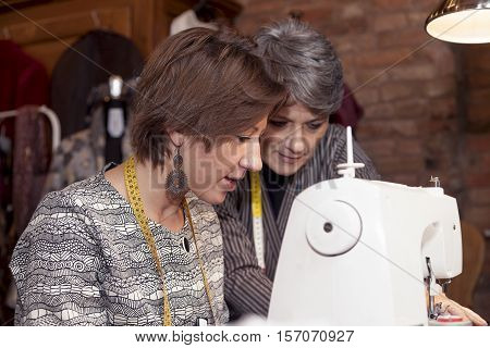 Dressmaker Couple Is Working With The Sewing Machine