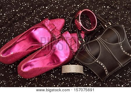Fashion woman accessories. Glittery shoes, black handbag clutch. Essentials fashion. Top view. Black background with sparkles. Beautyfully organized. Trendy. Isolated. Party.