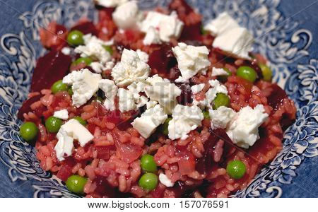 Beetroot risotto with cream goats cheese. Beet with rice and feta in blue bowl