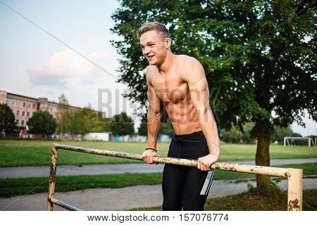 Muscular young man pull ups the horizontal bar. Street workout.