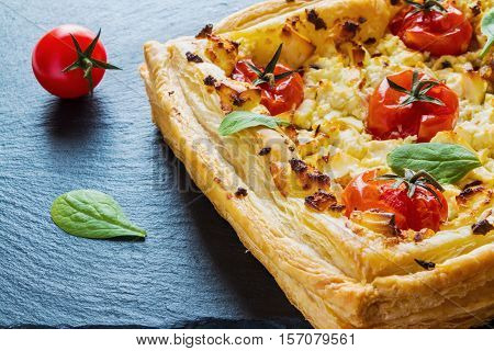Feta cheese tart made with butter puff pastry and whole cherry tomatoes. Black stone background.