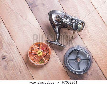 Fishing gear on wooden background. Silver coil spools of fishing line and yellow box for hooks