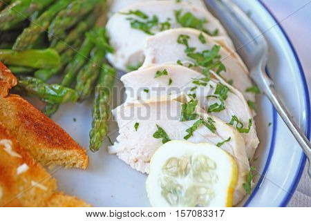 Plate of sliced poached chicken with garlic bread and sauteed asparagus