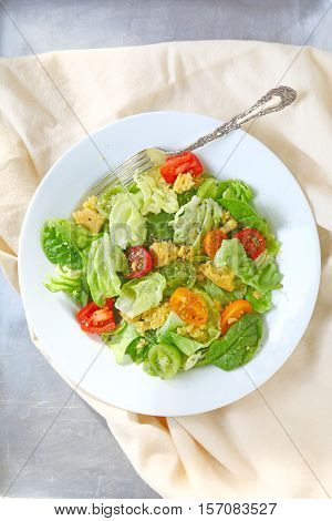 Salad of lettuce baby spinach and cherry tomatoes with crumbled cornbread