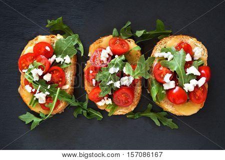 Crostini Appetizers With Cherry Tomatoes, Arugula, And Cheese, Above View On Slate