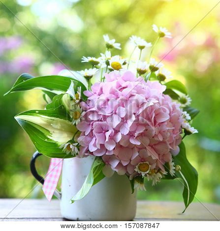cute bouquet with hydrangea and chamomile flowers close up photo on the green garden background square photo
