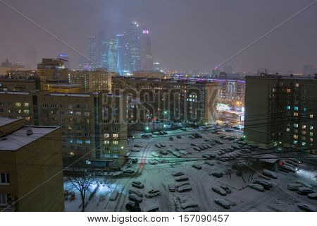 Residential area with buidlings, car parking in Moscow, Russia at winter, skyscrapers far away