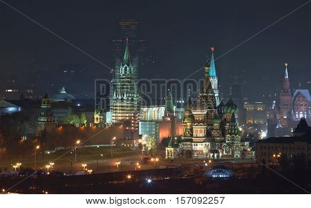 Kremlin wall, Spassky Tower being restored, Vasilevsky descent and St Basil Cathedral in Moscow, Russia at night