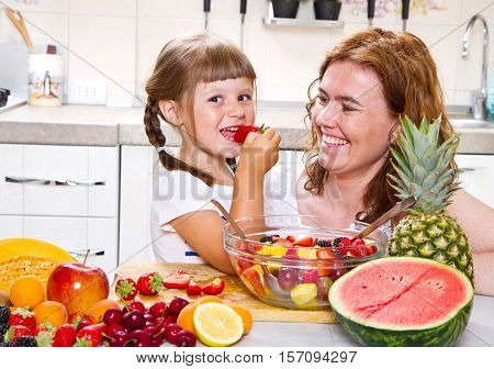 mother gives to the little girl a fruit salad in the kitchen.
