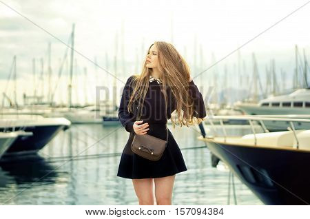 Beautiful blonde cute caucasian woman posing in harbor with luxury yachts on background. Girl wearing black fashionable skirt holding her hair.