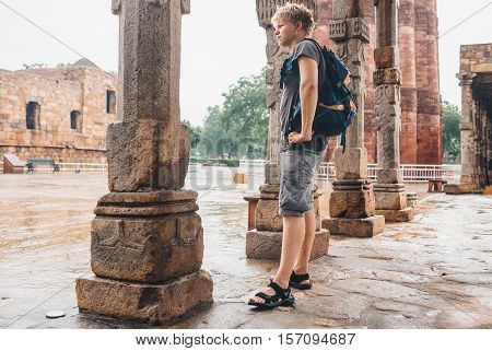 Young tourist man waits for intense rain to stop in the yard of Qutb Minar Complex in India New Delhi