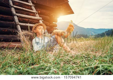 Boy snoozes lying on the ground late on summer afternoon