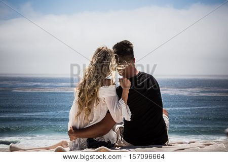 Lovely couple hugging on the beach and looking at the ocean on a sunny day