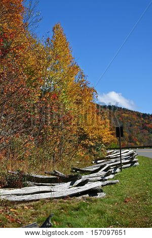 a split rail fence along a curve in the Blue Ridge Parkway in North Carolina, during autumn foliage season