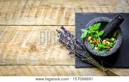 fresh herbs, avocado, nuts and mortar on wooden background top view