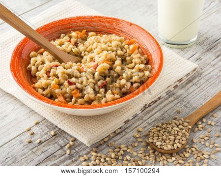 Pearl barley porridge with vegetables in an orange ceramic plate with a kitchen towel, pearl barley in a wooden spoon and glass of milk on a white wooden table