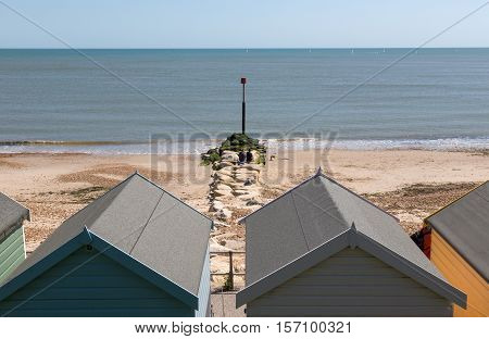 Looking through the beach huts, along the groin and out to sea.
