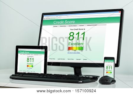 Computer Desktop With Digital Tablet And Mobilephone Showing Credit Score Online On Office Desk