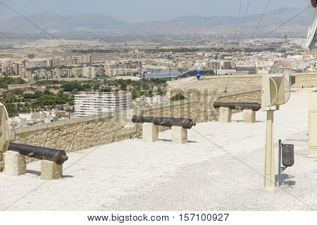 line of ancient cannons in the rampart of the castle of santa barbara with the city of alicante spain in teh background