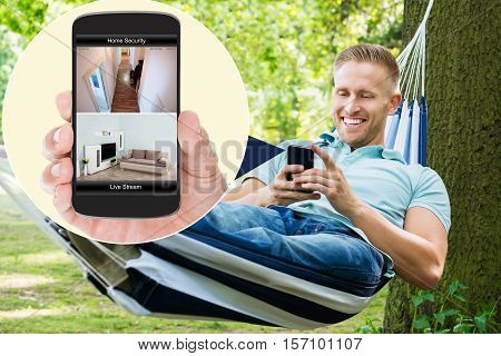 Young Happy Man Sitting On Hammock Looking At Home Security System On Mobilephone