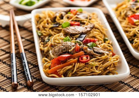 Lo mein with vegetables mushrooms and soy filets.