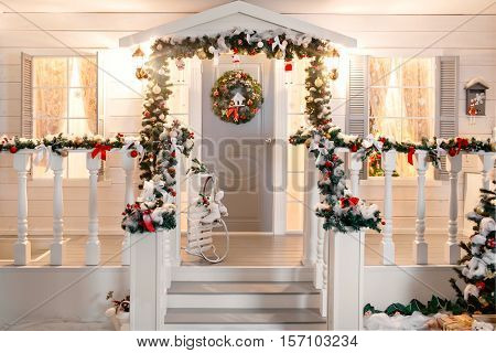 Green garlands of fir or pine branches with red and gold Christmas toys door on the veranda.