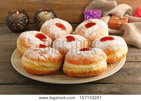 Plate with tasty donuts on wooden background. Hanukkah celebration concept