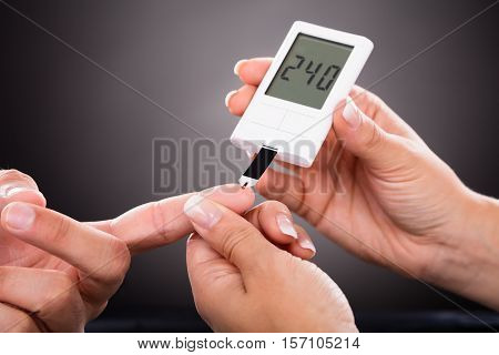Close-up Of A Doctor Checking Patient's Sugar Level With Glucometer