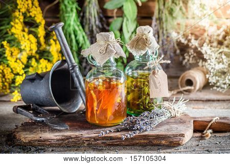 Therapeutic Tincture With Alcohol And Herbs On Old Wooden Table