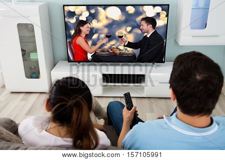 Young Couple Watching Romantic Movie On Television Together At Home