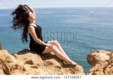 Young beautiful woman enjoying the sun by the ocean, sitting on a cliff
